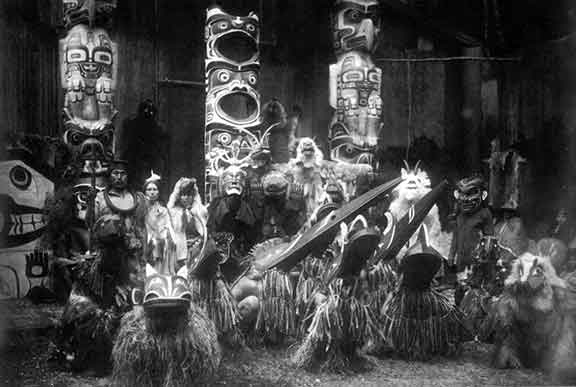 Kwakwaka'wakw dancers assembled for the sacred winter dance ceremonial.  Raven, sea eagle, mountain goat, grizzly bear, wasp, and orca clans are represented.  1914.  From