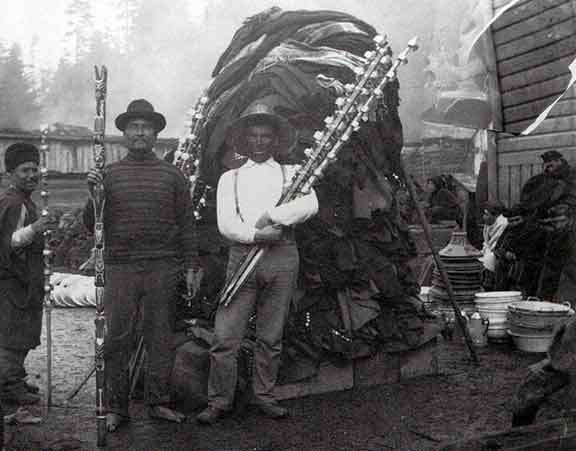 Figure 5 - Men posing with potlatch gifts to be distributed.  Note the silver bracelets on cedar poles, blankets, woven hats, and tin and enamel wares.  Circa 1910.  From